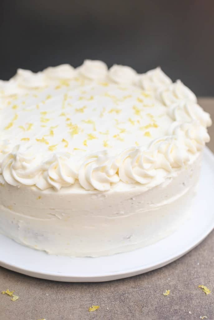An entire Lemon Cake frosted with Lemon Buttercream frosting on a white plate with piped edges.