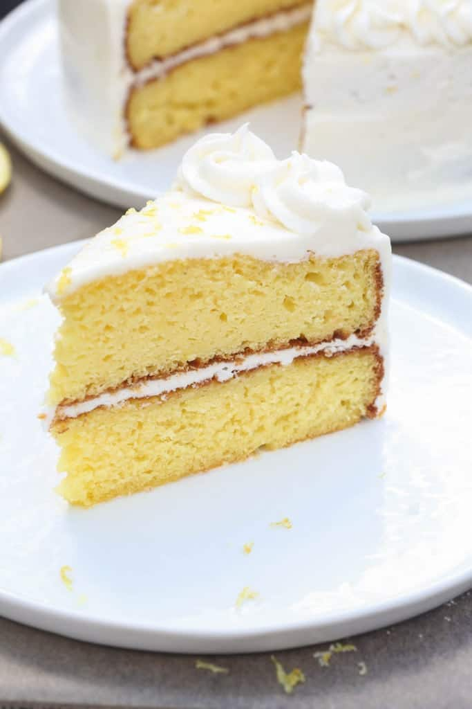 A slice of Lemon Cake with a light Lemon Buttercream frosting on a white plate.