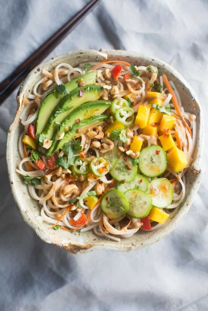 An overhead view of a bowl filled with rice noodles, cucumber, mangos, bell pepper, and avocado.