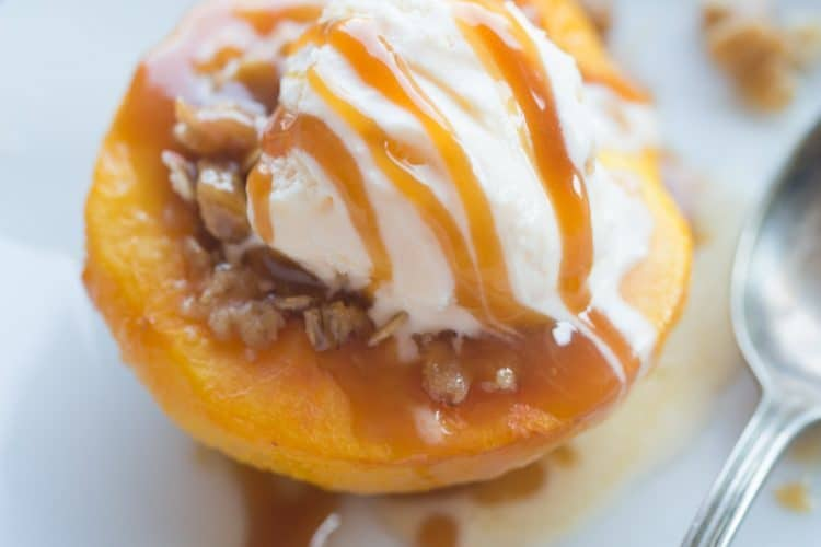 Warm and juicy baked peaches with a caramel oat crumble and vanilla ice cream! Baked peaches make the perfect light, warm and easy dessert!