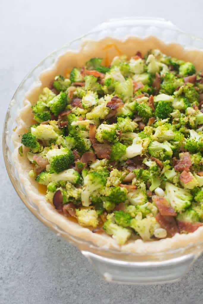 A glass pie dish with homemade pie crust that is filled with small pieces of broccoli and bacon.