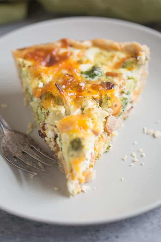 A triangular slice of a Broccoli Cheese Quiche with small pieces of bacon and broccoli sitting on a white plate.