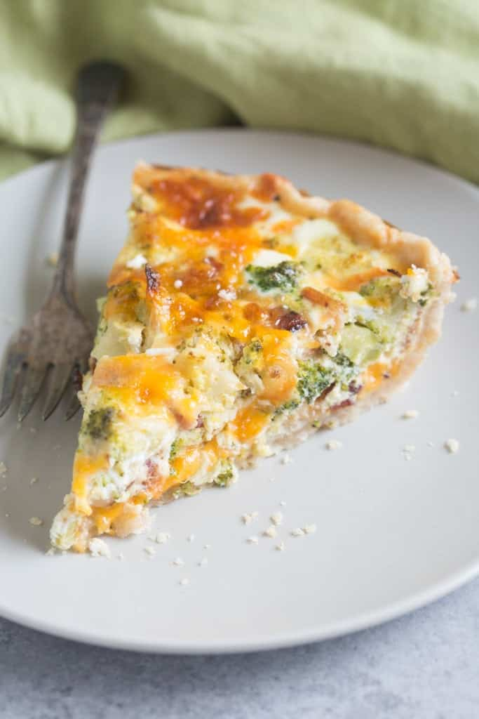 A slice of Broccoli Cheese Quiche in the shape of a piece of pie on a white plate