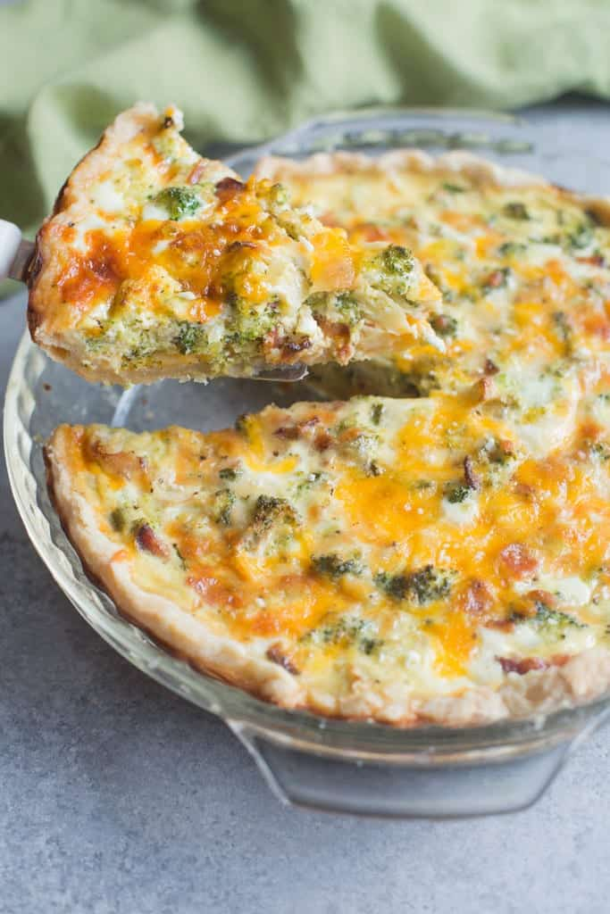 A glass pie dish filled with a baked Broccoli Cheese Quiche with one slice being taken away.