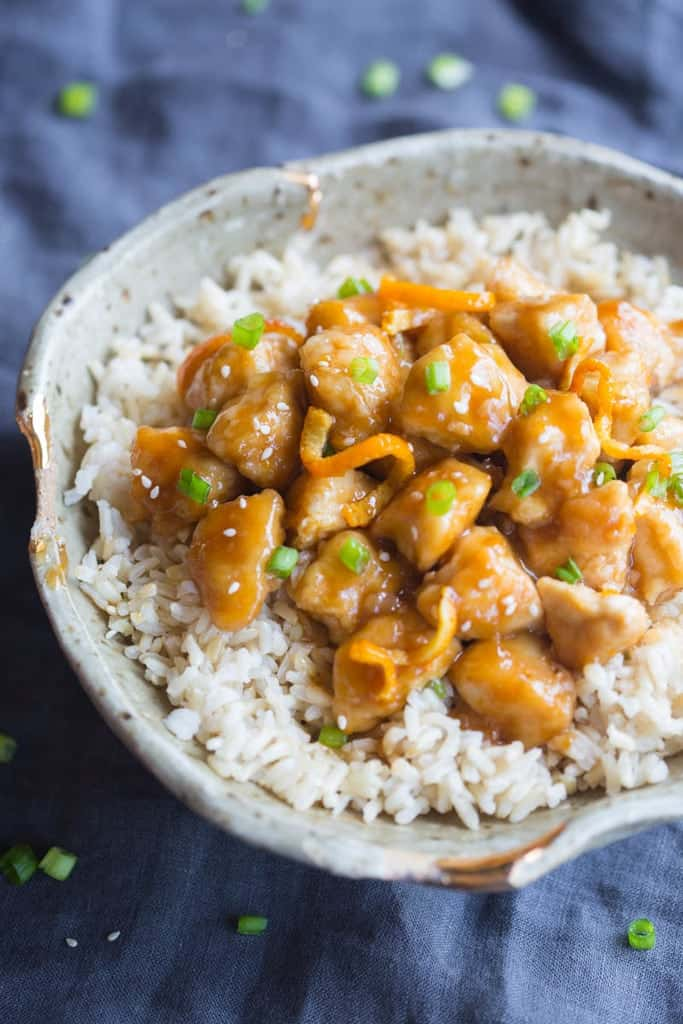 The left side of a bowl of brown rice with homemade orange chicken on top.