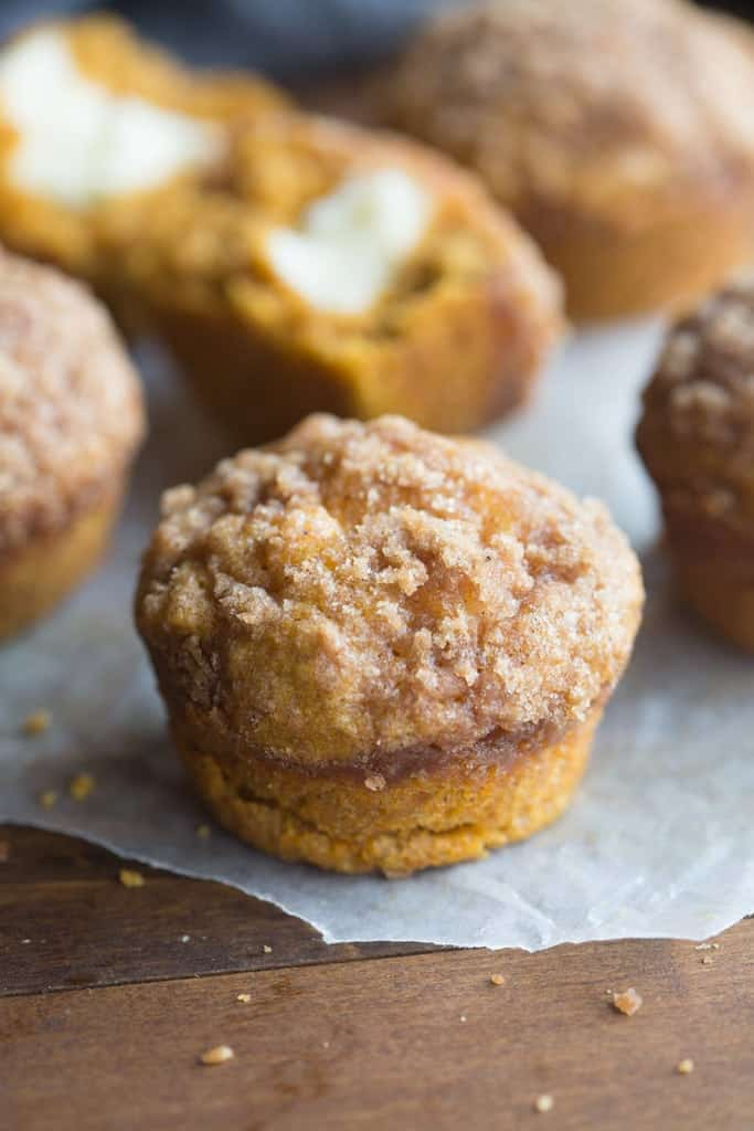 Pumpkin muffins with cream cheese filling on parchment paper.