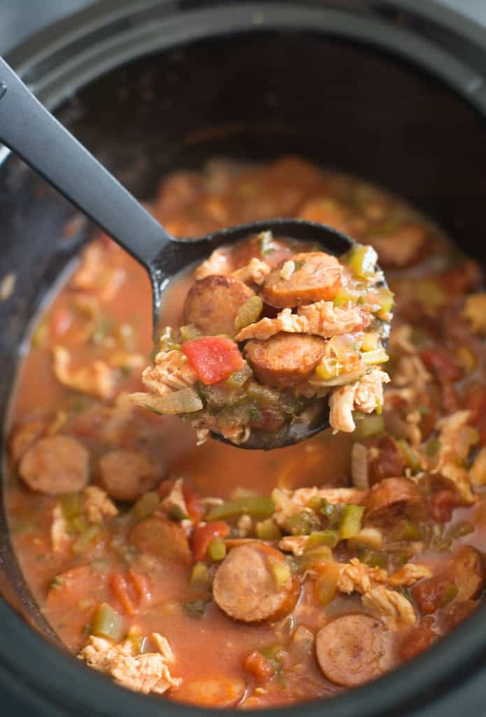 A ladle scooping out a spoonful of Slow Cooker Cajun Chicken and Sausage.
