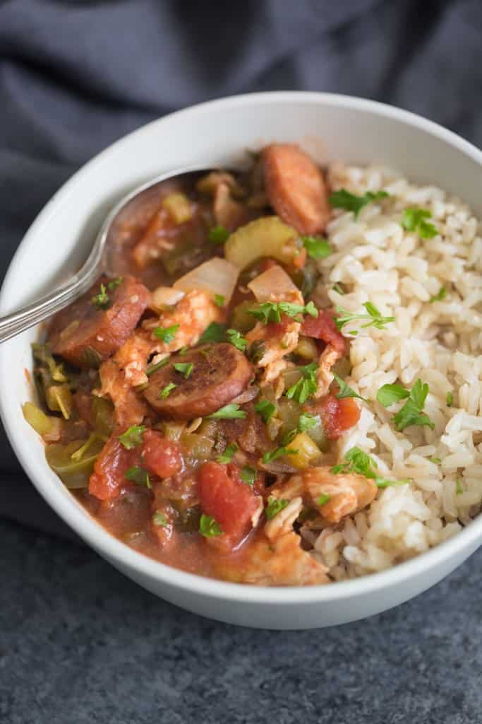 A spoon laying in a bowl filled with Slow Cooker Cajun Chicken, Sausage, and white rice.