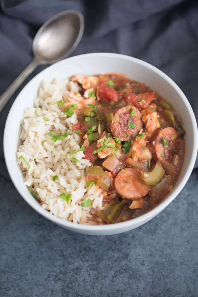 A bowl filled with Slow Cooker Cajun Chicken and Sausage and white rice.