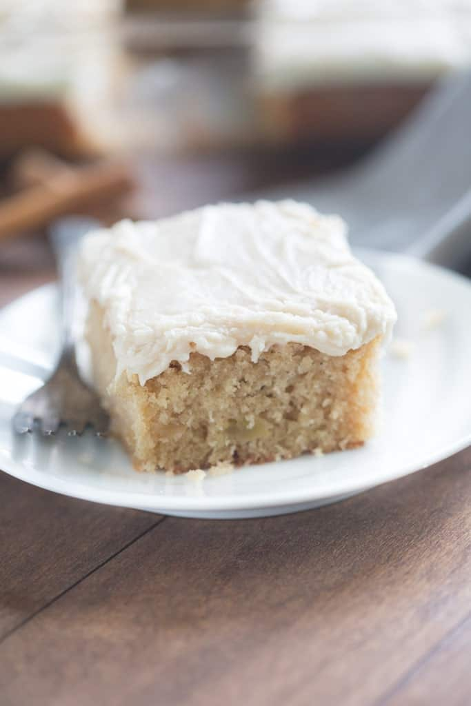 A white plate with one slice of Apple Spice Cake topped with Brown Sugar Cream Cheese Frosting.