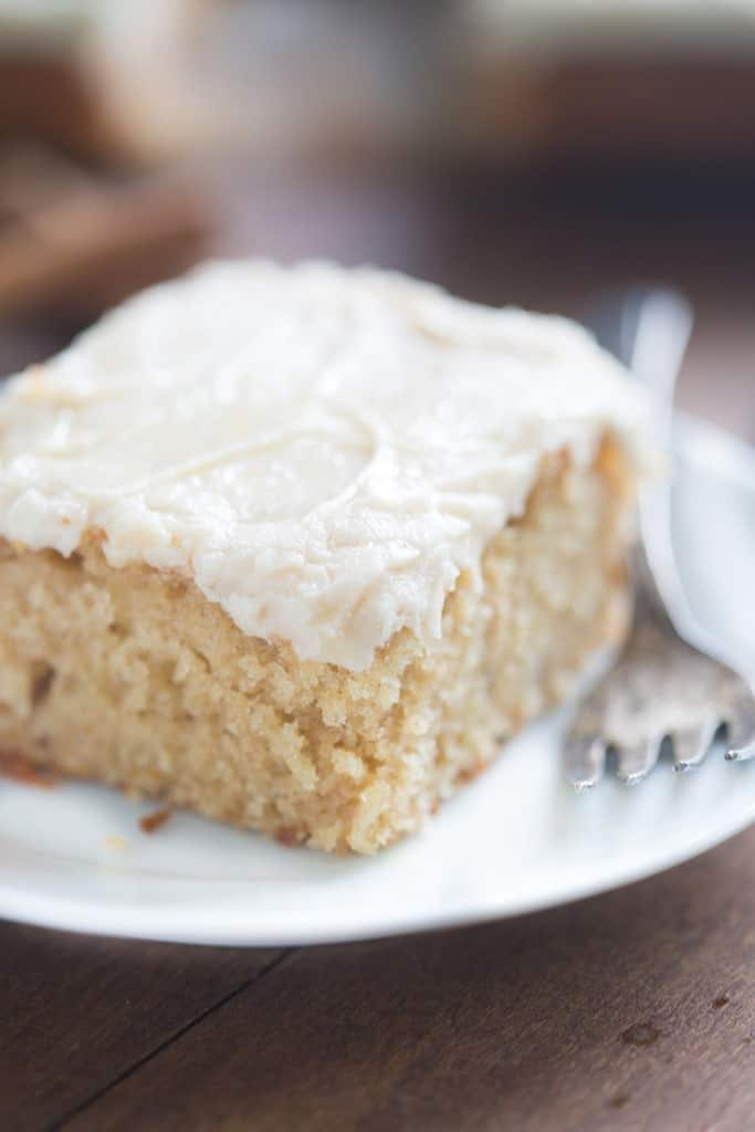 A close up of a slice of Apple Spice Cake covered in Brown Sugar Cream Cheese Frosting.