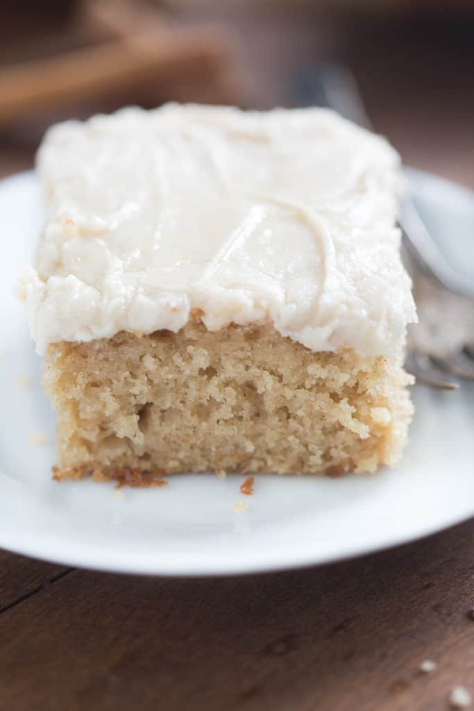 A slice of Apple Spice Cake with Brown Sugar Cream Cheese Frosting on a white plate