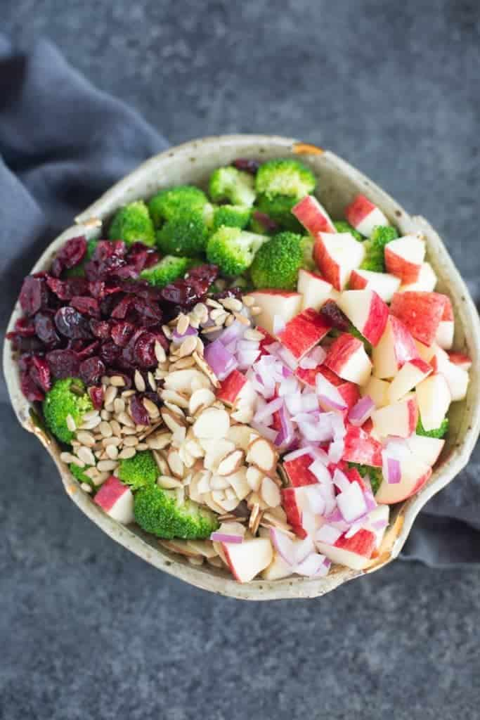 A bowl filled with blanched broccoli, apples, almonds, sunflower seeds, red onion, and craisins.