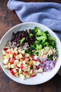Chopped applies, broccoli florets, onion, almonds and craisins in a bowl.