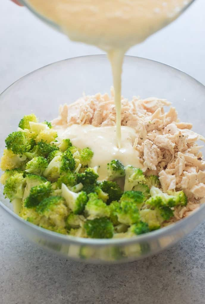Shredded chicken and steamed broccoli in a bowl with alfredo sauce poured on top.