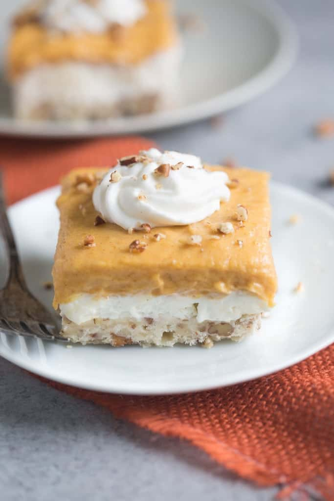 A square dessert with a pecan crust, cheesecake filling, and topped with pumpkin pudding.