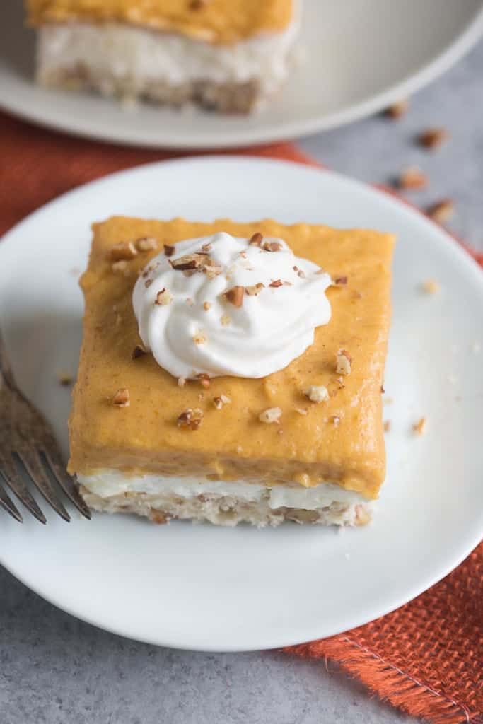 Pumpkin Dream Dessert is a layered pudding dessert with a soft shortbread crust, whipped sweet cream cheese layer and pumpkin pudding layer. We love this easy fall dessert! | Tastes Better From Scratch