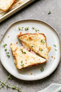 Croque monsieur sandwich cut in half and served on a plate.