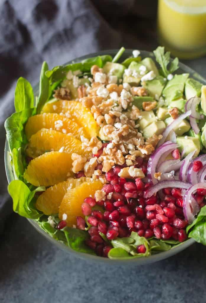 Spinach topped with Oranges, Pomegranates, walnuts, red onion, and avocado.