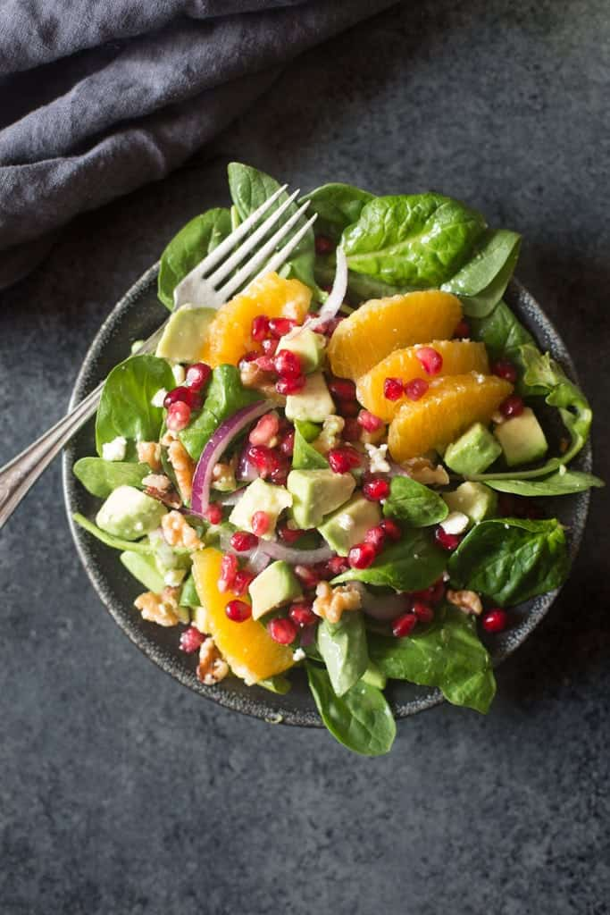 Oranges, Pomegranates, avocados, walnuts, and onion over a bed of spinach all resting in a bowl with a fork.