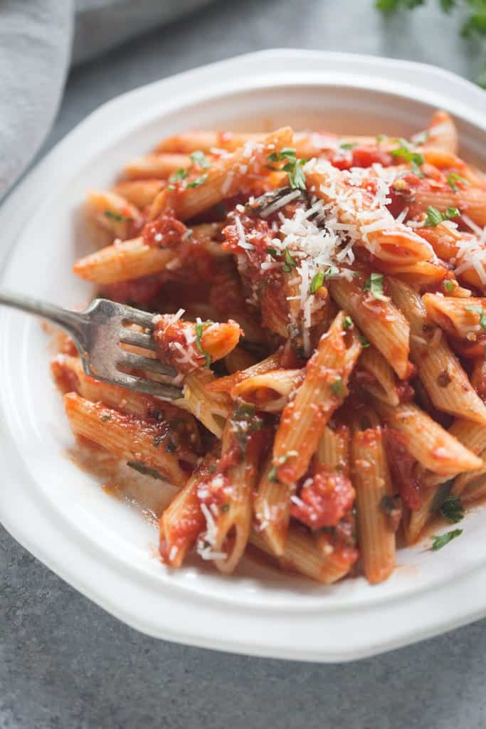 Penne Arrabbiata with a fork taking a bite.