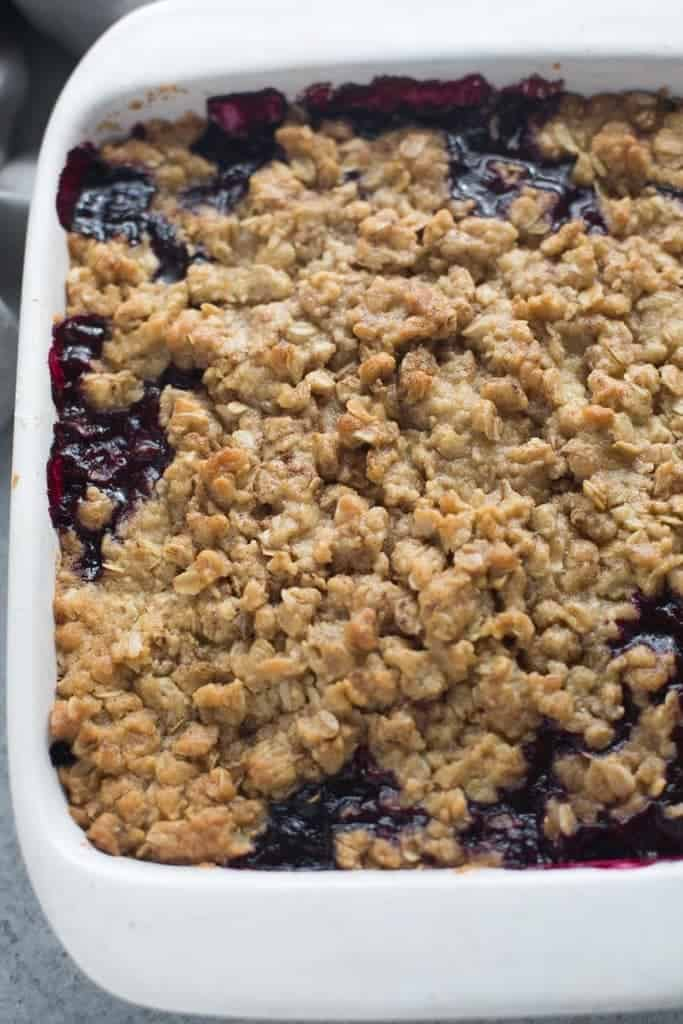 An 8x8 casserole dish filled with a berry mixture that is topped with a oat crumble.