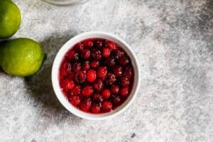 A bowl of cooked fresh cranberries in simple syrup.