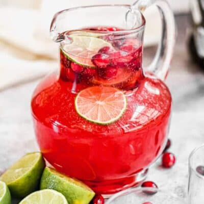 A pitcher of Christmas Punch with fresh cranberries and lime slices floating in it.