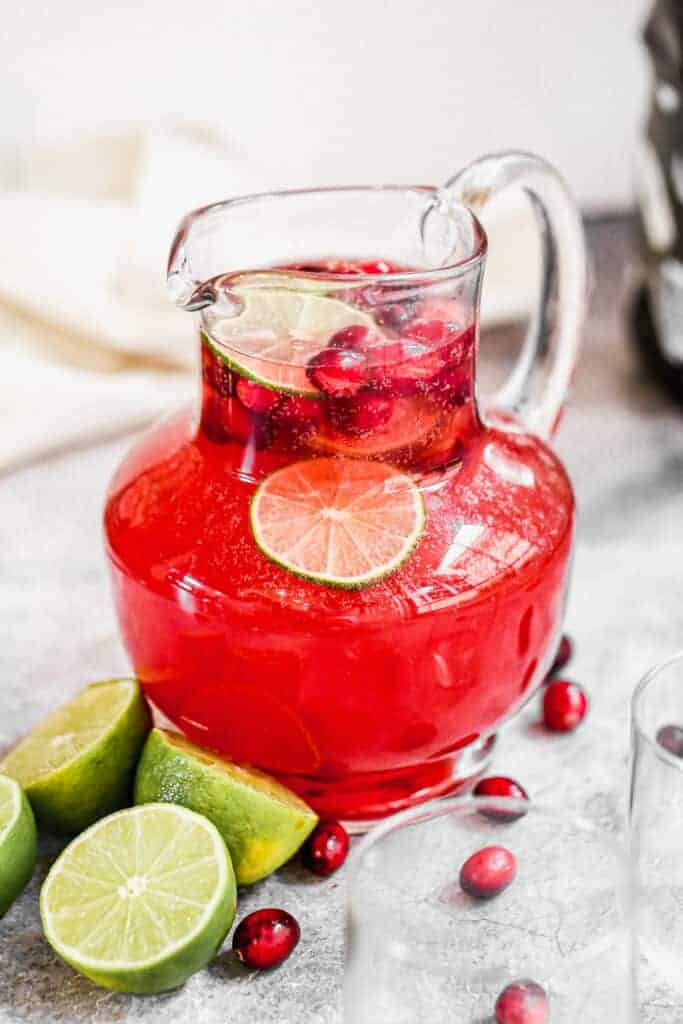 Christmas Punch served in a pitcher with ice, fresh cranberries and lime slices.