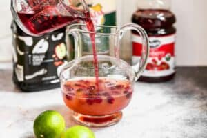 Cranberry juice being poured into a pitcher with fresh cranberries and simple syrup, to. make Christmas punch.