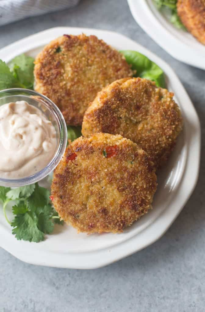 Three Crab Cakes on a plate with a parsley garnish and homemade dipping sauce.