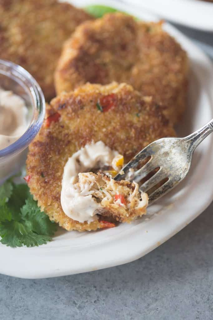 Chipotle mayo sauce being spread on a homemade crab cake.