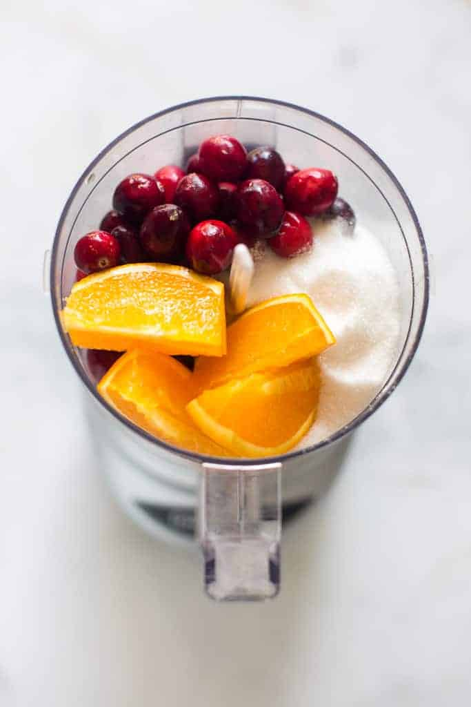 Food processor with whole cranberries, orange slices and sugar in it.