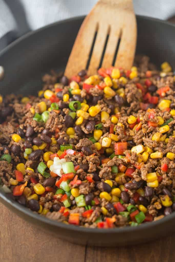 A skillet filled with ground beef, black beans, bell pepper, corn, and green onion.