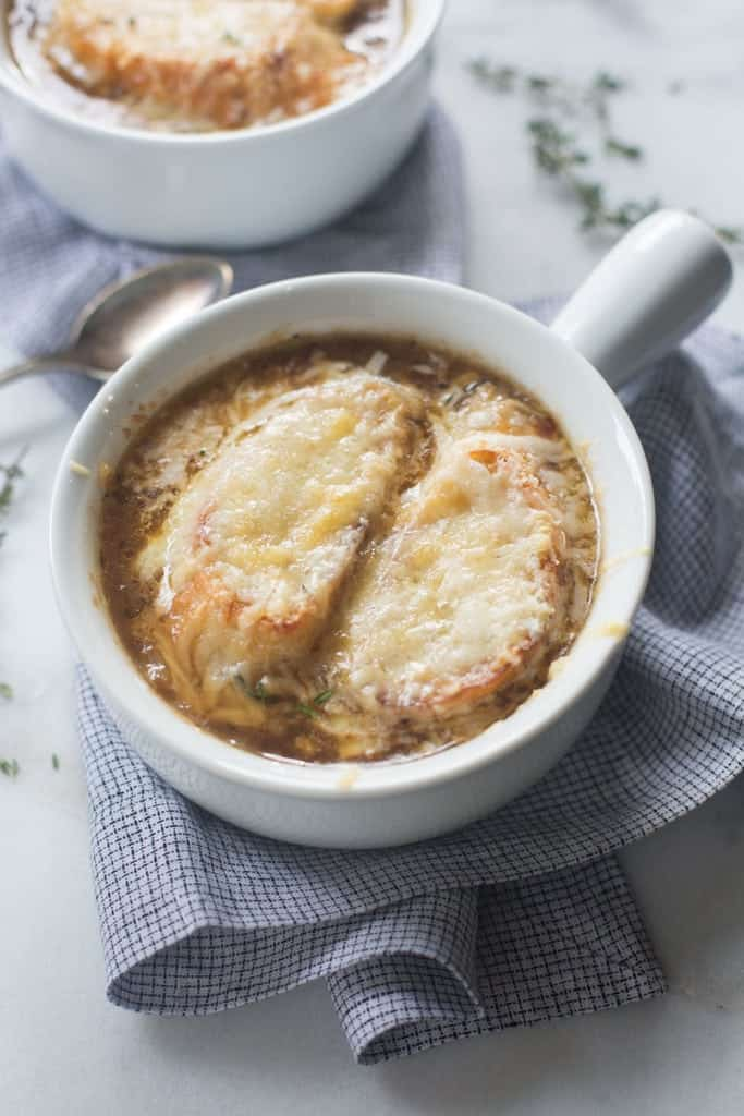 French Onion Soup topped with a french baguette and cheese.