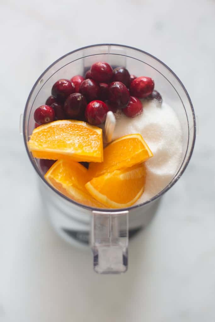 A food processor filled with oranges, cranberries, and sugar.