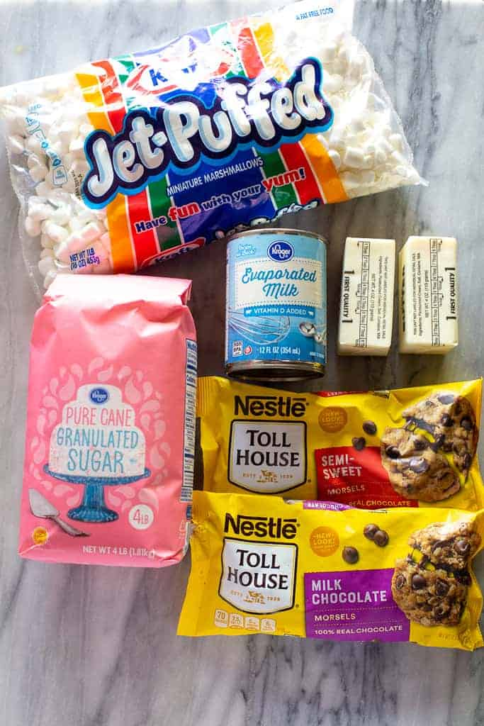 The ingredients to make fudge including mini marshmallows, sugar, chocolate chips, butter, and evaporated milk.
