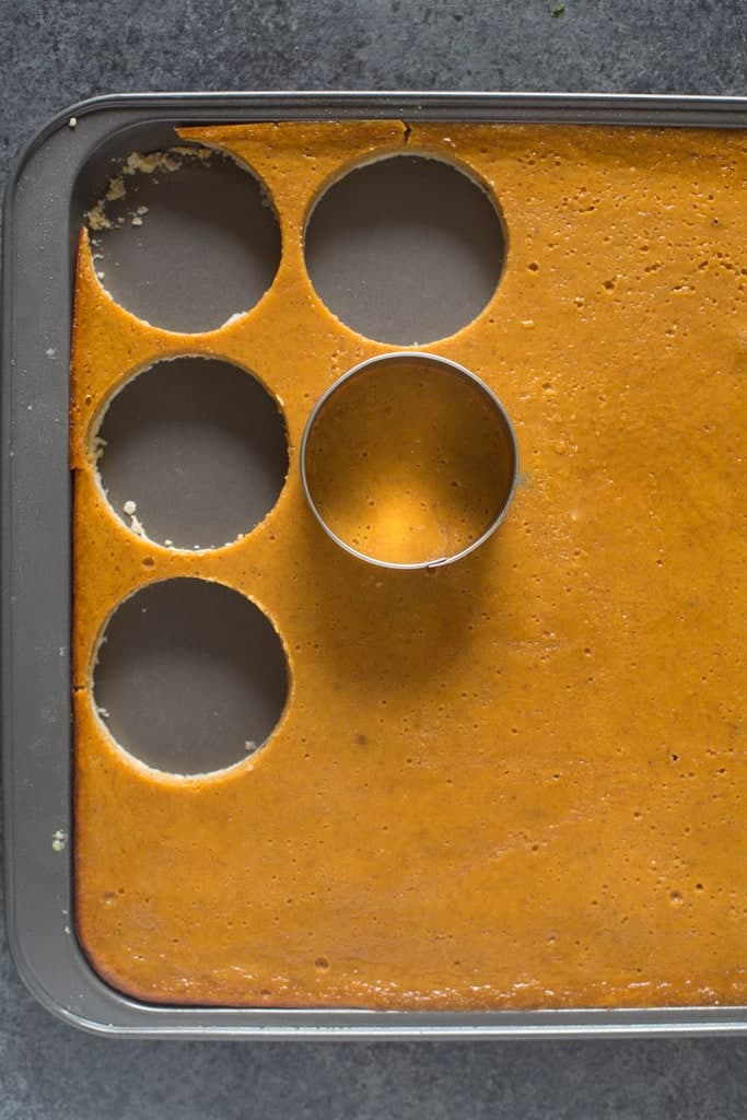 A sheet pan with pie crust and pumpkin filling being cut into small circles.