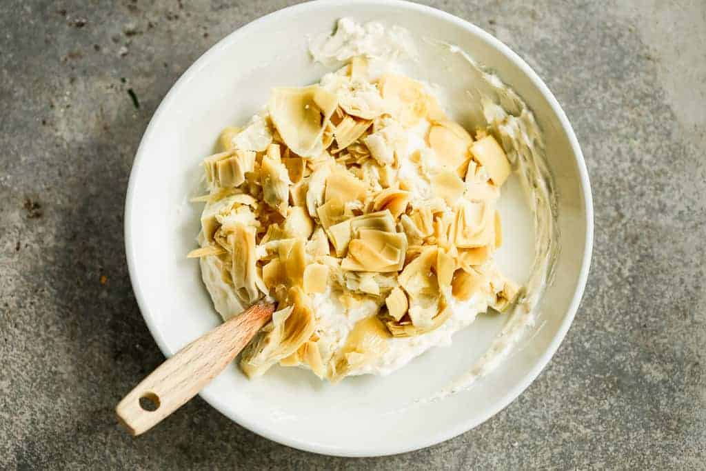 Marinated artichoke hearts added to mayo and cream cheese mixture to make artichoke dip.