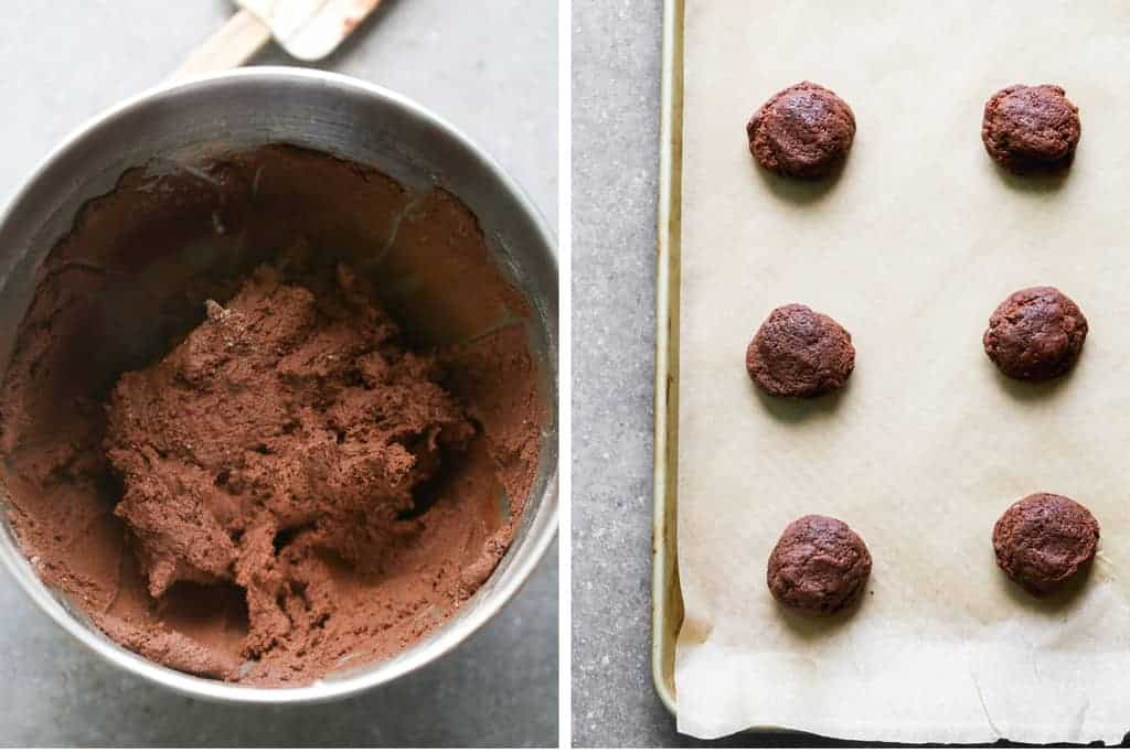 A bowl of chocolate cookie dough next to a cookie sheet with rolled cookie dough balls.