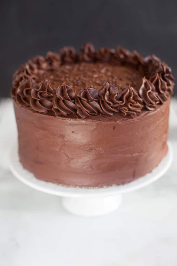 An entire Dark Chocolate Cake with chocolate frosting and piped frosting around the edges.