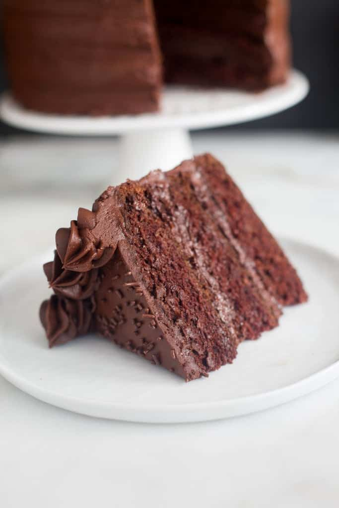 A slice of Dark Chocolate Cake with chocolate frosting on a white plate.