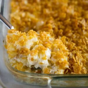 A spoonful of funeral potatoes being lifted from a 9x13 inch glass casserole dish.