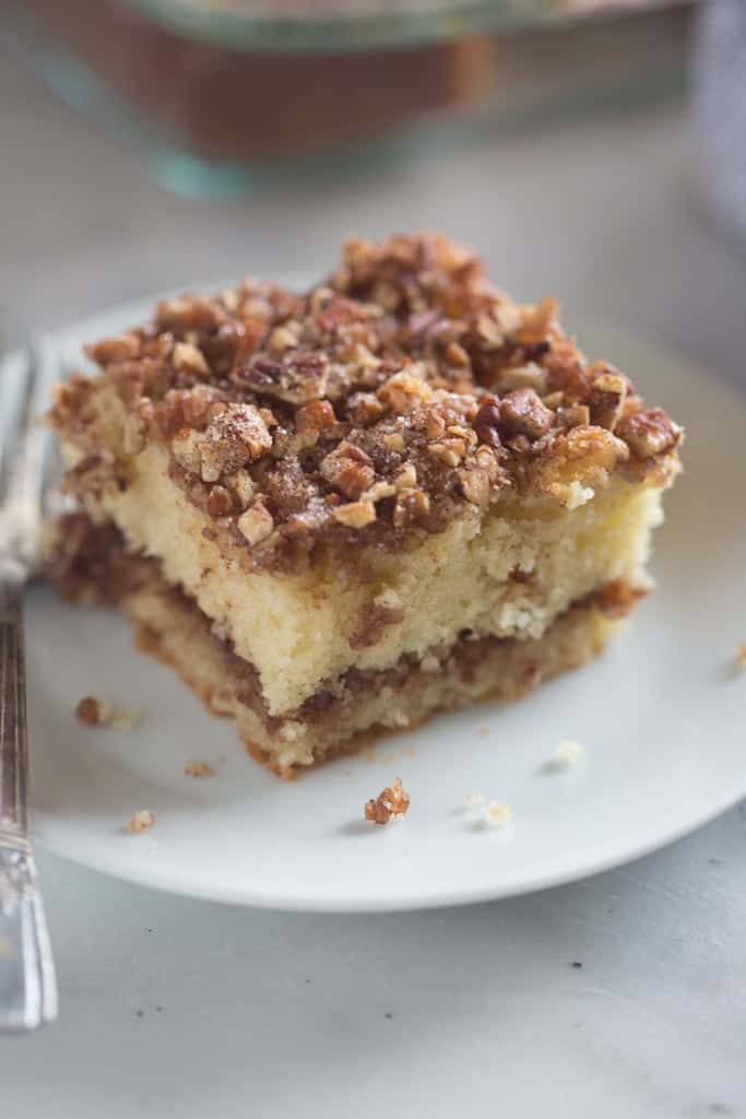 Sour Cream Coffee Cake with cinnamon pecan topping on a white plate.