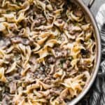 A skillet with stroganoff and egg noodles, cooked and ready to eat.