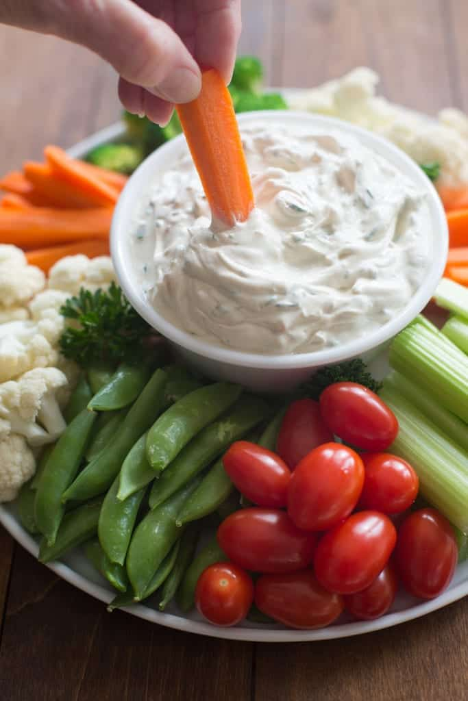 A plate full of assorted vegetables with a vegetable dip in the center and someone dipping a carrot into the dip.