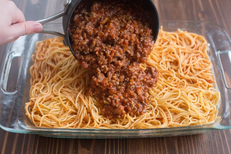 Cooked spaghetti noodles in a casserole dish topped with a ground beef meaty, spaghetti mixture.