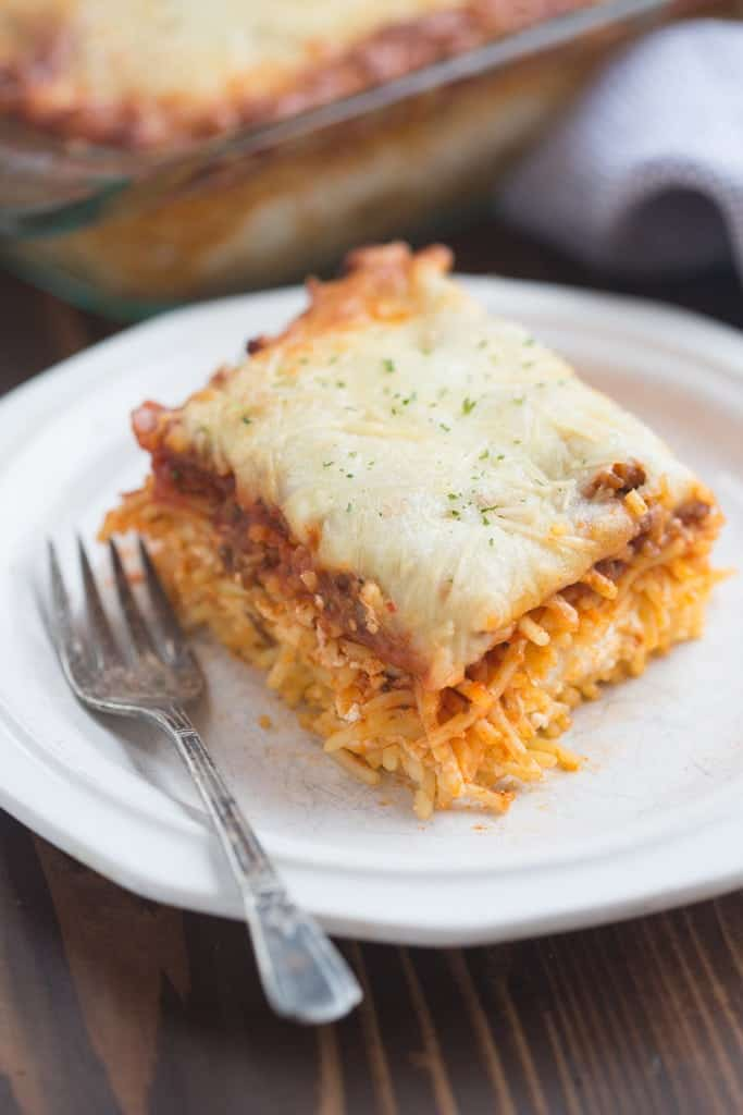 A plate with a square slice of spaghetti casserole with spaghetti topped with sauce and melted cheese.
