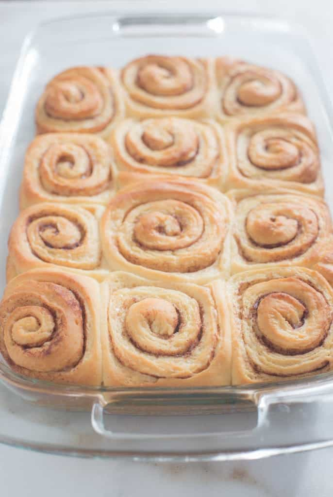 A glass baking dish filled with 12 big cinnamon rolls fresh out of the oven!