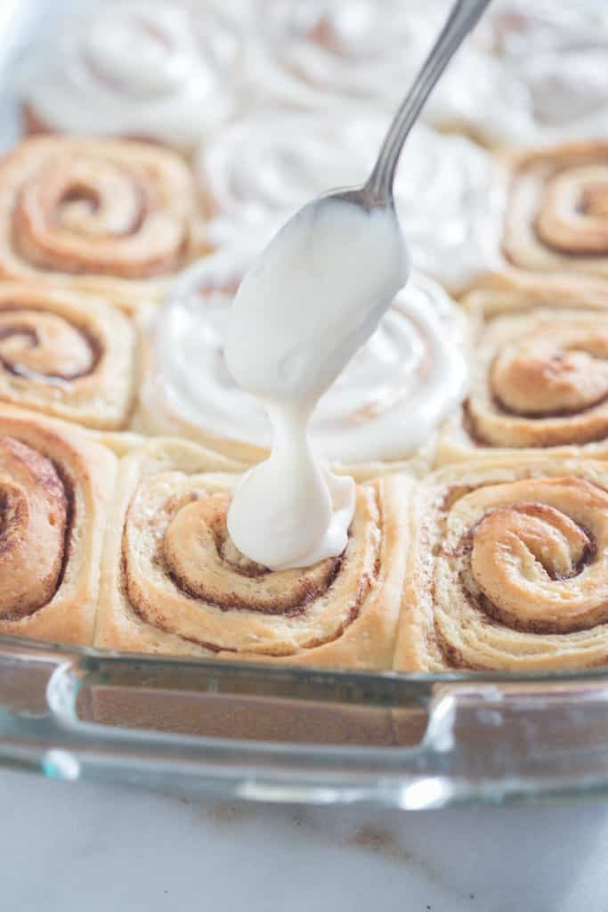 The front of a glass baking dish that is filled with cinnamon rolls and a spoon covering the top of the cinnamon rolls with cream cheese frosting.